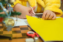 El niño cortó una estrella del papel de construcción, preparando artes de una Navidad, primer Fotografía de archivo