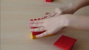 El niño crea la pequeña casa de ladrillos plásticos metrajes