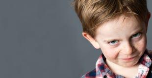 El niño dañoso joven que toma el pelo con el gruñido busca broma fotografía de archivo libre de regalías