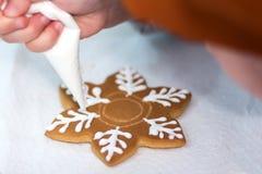 El niño da el adornamiento del pan de jengibre bajo la forma de un copo de nieve con el azúcar de formación de hielo usando un bo Fotografía de archivo