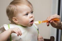 El niño da de comer a la boca Imagenes de archivo