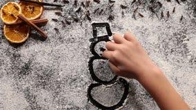 El niño da el dibujo de un muñeco de nieve en la harina almacen de video
