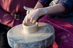 El niño da el trabajo con la rueda de cerámica de la arcilla Foto de archivo libre de regalías