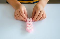 El niño da jellys del juego en la tabla blanca Imágenes de archivo libres de regalías
