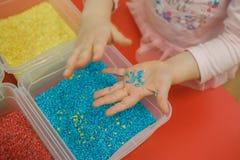 El niño da jugar con arroz coloreado en la caja sensorial Equipo educativo sensorial del ` s del bebé fotografía de archivo libre de regalías