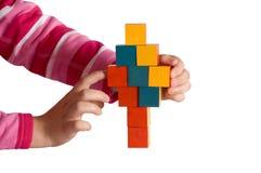 El niño da la construcción de una torre de bloques coloreados Foto de archivo libre de regalías