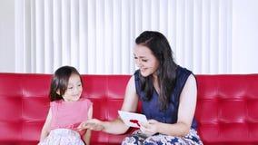 El niño da la tarjeta de felicitación para mimar en casa
