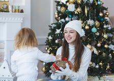 El niño da a mamá un regalo por la Navidad o el Año Nuevo en un fondo Fotos de archivo libres de regalías