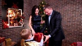 El niño da un regalo a los padres felicita a la madre y engendra un día de fiesta feliz, ` s Eve, fiesta de Navidad del Año Nuevo almacen de metraje de vídeo