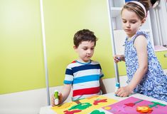 El niño de dos preescolares crea una imagen con formas Fotografía de archivo libre de regalías