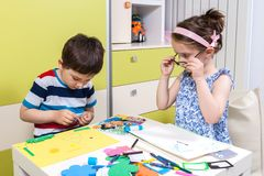 El niño de dos preescolares crea una imagen con formas Fotos de archivo
