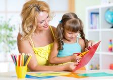 El niño de enseñanza del preescolar de la mujer feliz hace a mano Fotografía de archivo libre de regalías