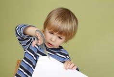 El niño de la actividad de los artes y de los artes de los niños que aprende cortar con Scissor Imágenes de archivo libres de regalías