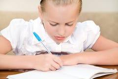 El niño de la colegiala escribe en un cuaderno Imagen de archivo libre de regalías