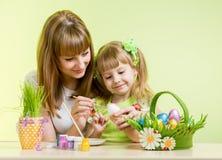 El niño de la madre y de la hija pinta los huevos de Pascua Imagen de archivo