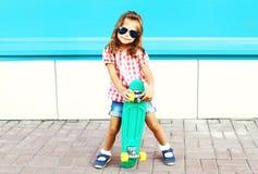 El niño de la moda se coloca con el monopatín en la ciudad en un colorido Foto de archivo libre de regalías