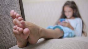 El niño de la muchacha con un teléfono celular hojea Internet almacen de video