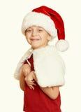 El niño de la muchacha en el retrato en blanco aislado, concepto del sombrero de santa del día de fiesta de la Navidad, amarillea Imágenes de archivo libres de regalías