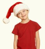 El niño de la muchacha en el retrato en blanco aislado, concepto del sombrero de santa del día de fiesta de la Navidad, amarillea Fotos de archivo libres de regalías