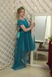 El niño de la muchacha en el vestido atractivo que se coloca al lado del espejo, admirándose Imagen de archivo