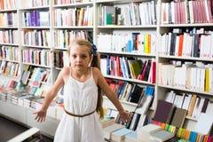 El niño de la muchacha pasmó muchos libros en una librería Fotografía de archivo libre de regalías