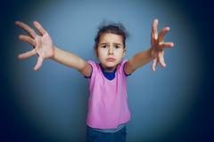 El niño de la muchacha pide manos en un fondo gris Imagen de archivo