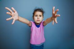 El niño de la muchacha pide manos en un fondo gris Fotografía de archivo libre de regalías