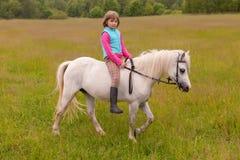 El niño de la niña camina en un caballo blanco en el campo al aire libre Foto de archivo