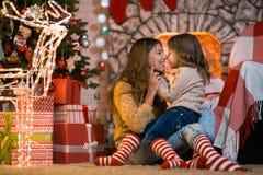 El niño de la niña en casa por la chimenea con la familia paren fotografía de archivo libre de regalías