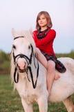 El niño de la niña en un vestido rojo se sienta a horcajadas en un caballo blanco Fotos de archivo libres de regalías