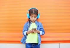 El niño de la niña escucha la música en auriculares y smartphone con Fotografía de archivo