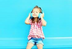 El niño de la niña escucha la música en auriculares Imágenes de archivo libres de regalías