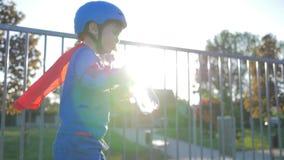 El niño de los deportes en casco y rodillos bebe el agua pura de la botella plástica al aire libre metrajes