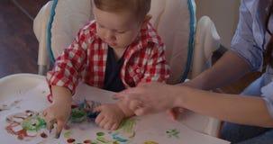 El niño del bebé está pintando con los fingeres de la palma usando la pintura coloreada de la mano almacen de metraje de vídeo