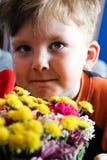 El niño del bebé huele el ramo de las flores foto de archivo libre de regalías