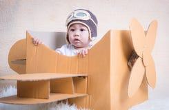 El niño del bebé vuela con el avión de la caja de cartón Imágenes de archivo libres de regalías