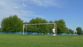 El niño del muchacho que se coloca en un campo verde golpea la bola con el pie metrajes