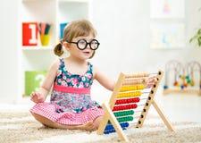 El niño del niño weared los vidrios que jugaban con el juguete del ábaco Imagen de archivo libre de regalías