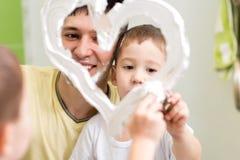 El niño del padre y del hijo dibuja forma del corazón en el espejo Foto de archivo libre de regalías