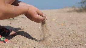 El niño derrama la arena en la playa Las manos de los niños sacaron un puñado con pala de arena, aumentado al top y vierten con l almacen de video