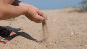 El niño derrama la arena en la playa Las manos de los niños sacaron un puñado con pala de arena, aumentado al top y vierten con l almacen de metraje de vídeo