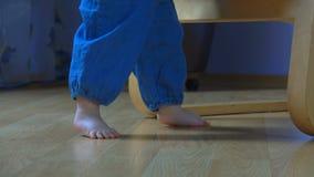 El niño descalzo está bajando de una butaca y está caminando incierto almacen de video