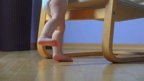 El niño descalzo está bajando de una butaca y de caminar almacen de video