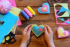 El niño detiene a una tarjeta del día de San Valentín del fieltro en sus manos El niño hizo a tarjetas del día de San Valentín de Fotografía de archivo libre de regalías