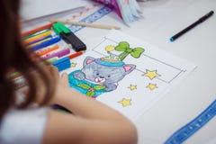El niño dibuja con el gatito de las pinturas Foto de archivo