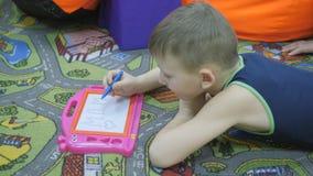 El niño dibuja en la pizarra con una pluma magnética almacen de video