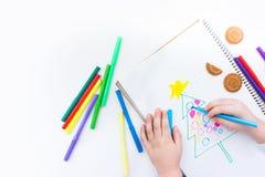 El niño dibuja un árbol de navidad con los lápices y el marcador coloreados Imágenes de archivo libres de regalías