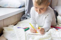 El niño dibuja un árbol de navidad con los lápices y el marcador coloreados Imagen de archivo