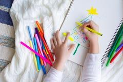 El niño dibuja un árbol de navidad con los lápices y el marcador coloreados Fotografía de archivo libre de regalías