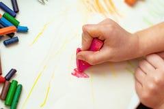 El niño dibuja una flor en el papel con los creyones de cera hechos con sus propias manos fotografía de archivo libre de regalías